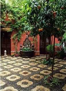 Patio with pebbles mosaics and orange trees in Cordoba patio festival in Spain