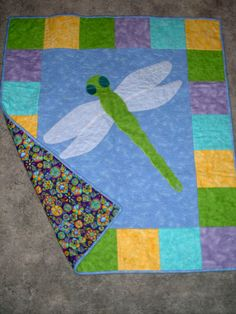 Dragonfly baby quilt by Maureen Eberhardt   Machine pieced and quilted from flannel fabric with crinkled drapery sheer appliqued wings, the original design was a gift for my friend's first granddaughter.