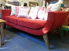 """Sofá """"U"""" 180x72 tapizado en pana roja, con asiento de placa soft y patas de madera."""