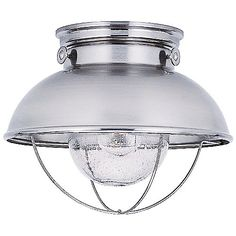 The Sebring Outdoor Flushmount by Sea Gull Lighting brings that undeniable nautical charm to your home décor. Its industrial-esque design features a smooth metal body (available in different finishes) with charming knob accents and an open parabolic cage at its base. Within the cage, a Clear Seeded Glass shade diffuses light from an inner source, eliciting a warm, shimmering ambiance that makes you feel you're right on the coast.