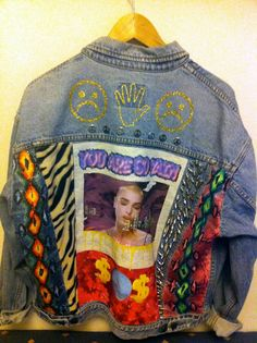 denim jacket with painted/stamped on symbols in gold glitter glue, peace sign pins, studs, snakeskin and tiger fabric, printed patches