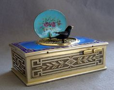 Fine French singing bird box by Juvinia of France in silver gilt and sky blue guilloche enamel.The sides are cast in sliver in a key pattern with laurel leaves. Similar edging to the top but with beautiful and perfect sky blue guilloche enamel inset. The top of the lid hand painted with a Swiss mountain and lake scene in irridescent enamel. Underneath the lid are painted roses on a blue background..... Gavin Douglas Antiques
