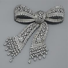 A DIAMOND BROOCH Of openworked tied ribbon bow design, decorated with foliate motifs set throughout with millegrain-set brilliant-cut diamonds. Edwardian or Edwardian style.