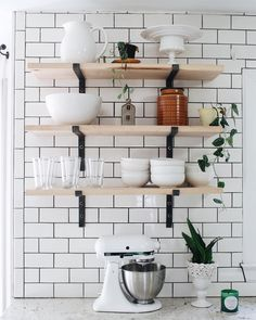 White subway tile and natural wood open shelving