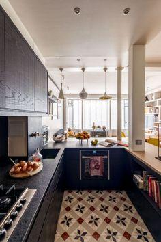 Sombre et très moderne, la cuisine se détache du salon. Elle ne s'isole pas pour autant : le sol en carreaux de ciment faisant le lien entre ces deux espaces
