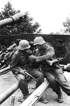 Two German soldiers sit on top of what looks like to be a 7.5cm Pak 41 Anti-Tank gun.
