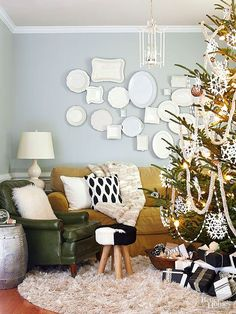 Layers of texture in this living room make you want to stay a while. White plates and platters on the wall function well as an accent during the holidays but are also a great focal point year-round. Pom-pom garland and classic snowflake ornaments unite the tree with the room's decor.