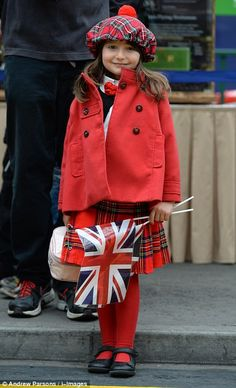 A young girl wears tartan outside the station while waiting to greet Her Majesty