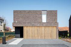 Moderne nieuwbouwvilla met warme materialen zoals gevelsteen en hout.