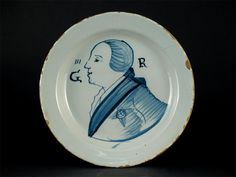 A rare Lambeth Delftware Royal portrait dish, painted in blue with George III in profile wearing a sash & The Order of the Garter between the initials 'GR' below 'III'. c.1761, 22cm.  Cf. J C Austin, British Delft at Williamsburg, p.140, no.190. It is likely that the portrait by Jeremiah Meyer is the likely source. The existence of a companion plate depicting Queen Charlotte Sophia of Mecklenburg-Strelitz suggests these plates were made at the time of their marriage in 1761.