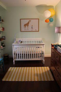 white crib, dark floor, gentle gender-neutral brights