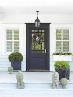 Navy front door. Like the offset plants and the idea of statues