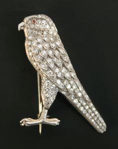 A diamond brooch designed as a bird of prey, pavé set with circular cut diamonds, with a cabochon red gem set eye.