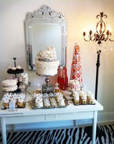 Current Sweet Table at the Connie Cupcake Design & Devour Studio..lucky people in the room!...Love the two white Fleur De Lis, Do they sit atop cupcakes or are  they decorations the two small white Fleur De lis at the base of both sides of the silver cake stand.....