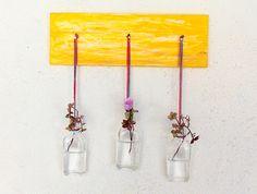 3 mini garrafas de vidro presas com fios coloridos em madeira pintadinha de amarelo. Um charmoso jardim suspenso! <br> <br>A madeira pode ser também turquesa, vermelho, pink, preto ou branca.