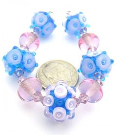 """Quantity: 9  Size: Approx. 6x9mm to 10x15mm (6mm = 1/4"""")  Hole Size: 1-1/2mm made on 1/16"""" mandrels  Colors: Dark Aqua, Pink Lavender & White  Accent Beads: 18 - 4mm Pink Lead Crystal Bicones    Eric's gorgeous bubble-in-bubble & plunged-bubble beads in beautiful Aqua & Pink Lavender for sweet Spring fashion designs. Kiln annealed, carefully cleaned & thoroughly inspected for your beading pleasure in beautiful West Tennessee. Colors may vary from monitor to monitor. Please contact us if you…"""