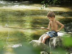 Фото Мальчик, сидя на камне, ловит рыбу удочкой, вырезанной из ветки дерева и примотанной к ней толстой леской
