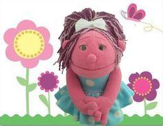 Títere niña de 30 cm, color rosa, vestido de color celeste con lunares blancos, cabello de lana tricolor, lazo blanco. (código NA-21)