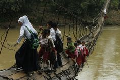Students hold on to the side steel bars of a collapsed bridge as they cross a river to get to school at Sanghiang Tanjung village in Lebak regency, Indonesia's Banten village January 19, 2012.