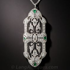 Art Deco Platinum, Diamond and Emerald Pendant. Originally designed as a convertible pendant/brooch combination, this exquisite Art Deco masterpiece was simplified by its former owner into a full-time pendant necklace. The beautiful, diamond bordered, platinum plaque highlights a sparkling trio of marquise diamonds which, along with fancy diamond-set flourishes overlay finely milgrained louvers. Four triangular emeralds add a dash of color to this splendid Jazz Age jewel.