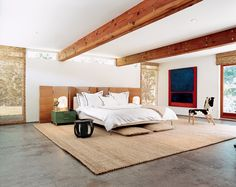 In the bedroom of Ione Skye's Case Study house in Los Angeles, her former partner and decorator David Netto turned Skye's former art studio into the Master bedroom, and made the concrete-floored room feel warm and inviting by using natural fiber on the floors and windows, and adding handmade objects such as a stool from Mali.