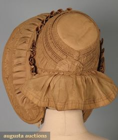 TAN SILK DRAWN BONNET, 1840s  Go Back Lot: 572 April 2006 Vintage Clothing & Textile Auction New Hope, PA All original, trimmed w/ lace and cloth flowers inside brimAugusta Auctions
