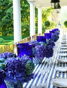 Blue hydrangeas, cobalt hurricanes, striped tablecloth - Carolyne Roehm