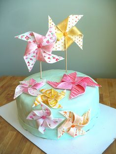 Pinwheel cake tutorial. The pinwheels are made from fondant.  http://www.clockworklemon.com/2012/02/pinwheel-cake-tutorial-.html#