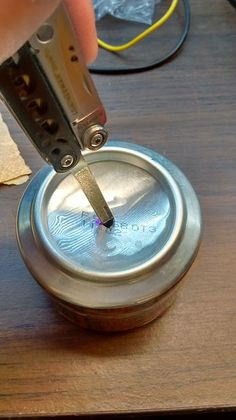"""Designate one tin cup as the inside piece, and the other as the outside piece. Lightly crimp the top edges of the inside can.  Face the two """"cups"""" together, and gently press and wiggle one inside the other. Be careful to avoid cutting yourself, since sheet metal can be incredibly sharp! Continue working them together until there is a tight pressure fit, and no further movement is possible.  (Optional) On the spot where a bare edge connects with the toPicture of Step 4: Puncture holes for…"""