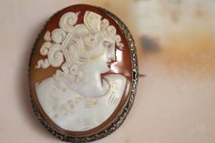 "Roman hand-carved shell cameo set in 800 silver filigree brooch. Locking clasp. Country of Origin: Italy Materials:800 silver/shell Size:1.62"" W x 2.12"" H Color/Finish:salmon/silverCondition: Very Goo"