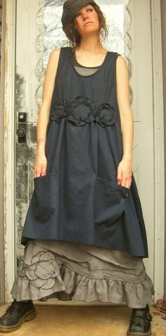 Short black dress with black fabric flowers over taupe sleeveless dress with ruffle and fabric flowers over black tank