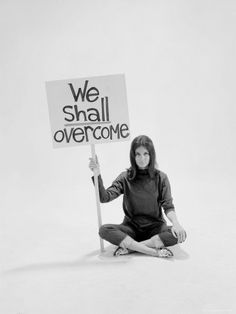 """Writer Gloria Steinem Sitting on Floor with Sign """"We Shall Overcome"""", dated 1965. (LIFE Magazine)"""