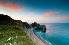 Durdle Door, Dorset, England. Durdle Door is one of the most photographed landmarks along the Jurassic Coast. This rock arch in the sea was formed as a result of the softer rocks being eroded away behind the hard limestones, allowing the sea to punch through them. #JetsetterCurator