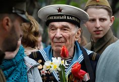 Russian World War II veteran Yevgeny Ermolayev (85) holds flowers during Victory Day in Moscow, Russia, on May 9. The Soviet Union lost an estimated 26 million people in the war, including 8.5 million soldiers. Russia commemorates the 1945 defeat of Nazi Germany on May 9. (Mikhail Metzel/Associated Press)