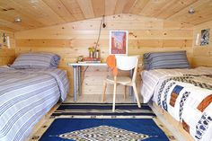 The owner of this DIY Wyoming Home sewed three sets of twin bedding from larger sheets. Recycled cans sans labels corral pencils on one of the desks.