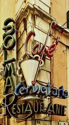 rotulo de una cafe restaurante,  muy llamtivo por sus colores en los rotulos con verde, rojo, azul, y una taza en el medio que es rodeada por todas las palabras de los rotulos.  Alejandro Estevez