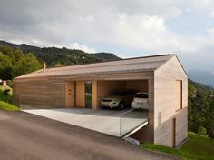 The timber house with copper roof is set in the steep meadows below the residential street. Houses On Slopes, Structural Insulated Panels, Hillside House, Copper Roof, Built In Furniture, Timber House, Garage Design, House On A Hill, Prefab Homes