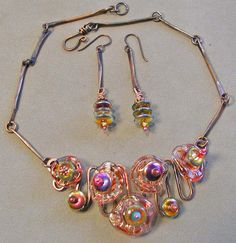 Lampwork glass discs incorporated into a copper wire frame and links.  All work by the artist