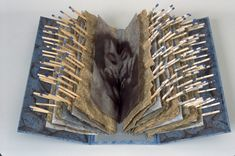 Robbin Ami Silverberg embeds matchsticks between sheets of paper in her artists' book, From Dreams to Ashes.