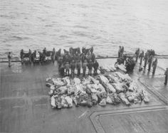 The remains of US sailors killed during a kamikaze attack on aircraft carrier USS Saratoga (CV-3) are awaiting their burial at sea. The attack occured on Feb 21, 1945. The Saratoga suffered 123 killed, 192 wounded and 42 planes destroyed and pushed overboard. She was immediately ordered back to the US for repair of the serious damage she had suffered.