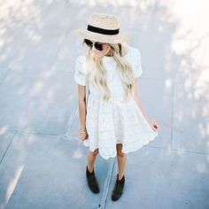 A pretty lace dress, ankle boots, and a straw hat.