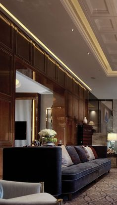 Rich timber panelling and colonial-style dusky blue sofa. The glamorous work of Steve Leung who designed Shangri-La at the Shard, London, UK