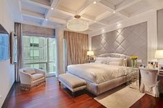 White coffered ceiling with tiled pillar that sparkles in the light of the chandelier. Each wall has varying textures and patterns.