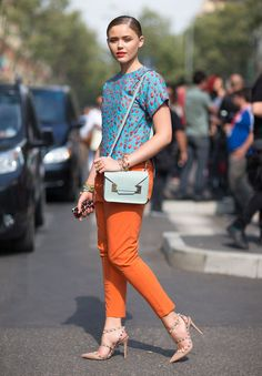 Milan Fashion Week spring 2014, Street style. Light blue and orange patterned top, orange pants, mint coloured Sophie Hulme bag and strapped nude Valentino shoes.