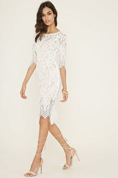 This sheer floral lace dress features 3/4 sleeves, a round neckline, a contrast removable slip underneath, scalloped eyelash lace trim, a concealed side zipper, and a back cutout.