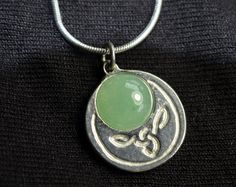 "This is a pretty little Irish pendant in it's original box.  The pendant and necklace are ""Celtic Silver"" The stone is a smooth half sphere, but there is no information on what the stone is made from. The pendant measures .75"" across and the necklace is 18"" long.  The necklace does appear to have a couple of kinks in it that may be able to be straightened."