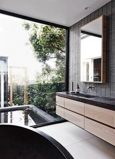 A gorgeous bathroom with floor to ceiling window, tiled wall, and wood cabinetry