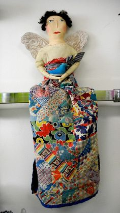 From Kati Koos - This hand made folk art doll has an antique quilt made into a dress and is holding a little blue bird (of happiness???)