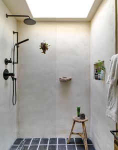 """The """"Rick Owens–inspired"""" bathroom features a concrete shower stall, vintage Batchelder tile from the 1920s, and a rock from Big Sur that the couple embedded into the wall as a soap dish."""