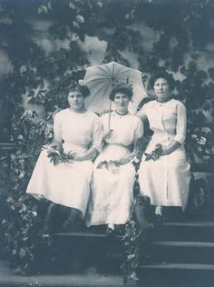 Three women wearing white dresses, with the woman in the center holding a parasol.  Photo taken at Cal Calvert's City Park Gallery in Portland, Oregon.  Excellent condition - please see scans to best determine condition. Real Photo Postcard, with Cyko stamp box. Circa 1910.